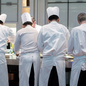 Group of chefs in white uniform busy to