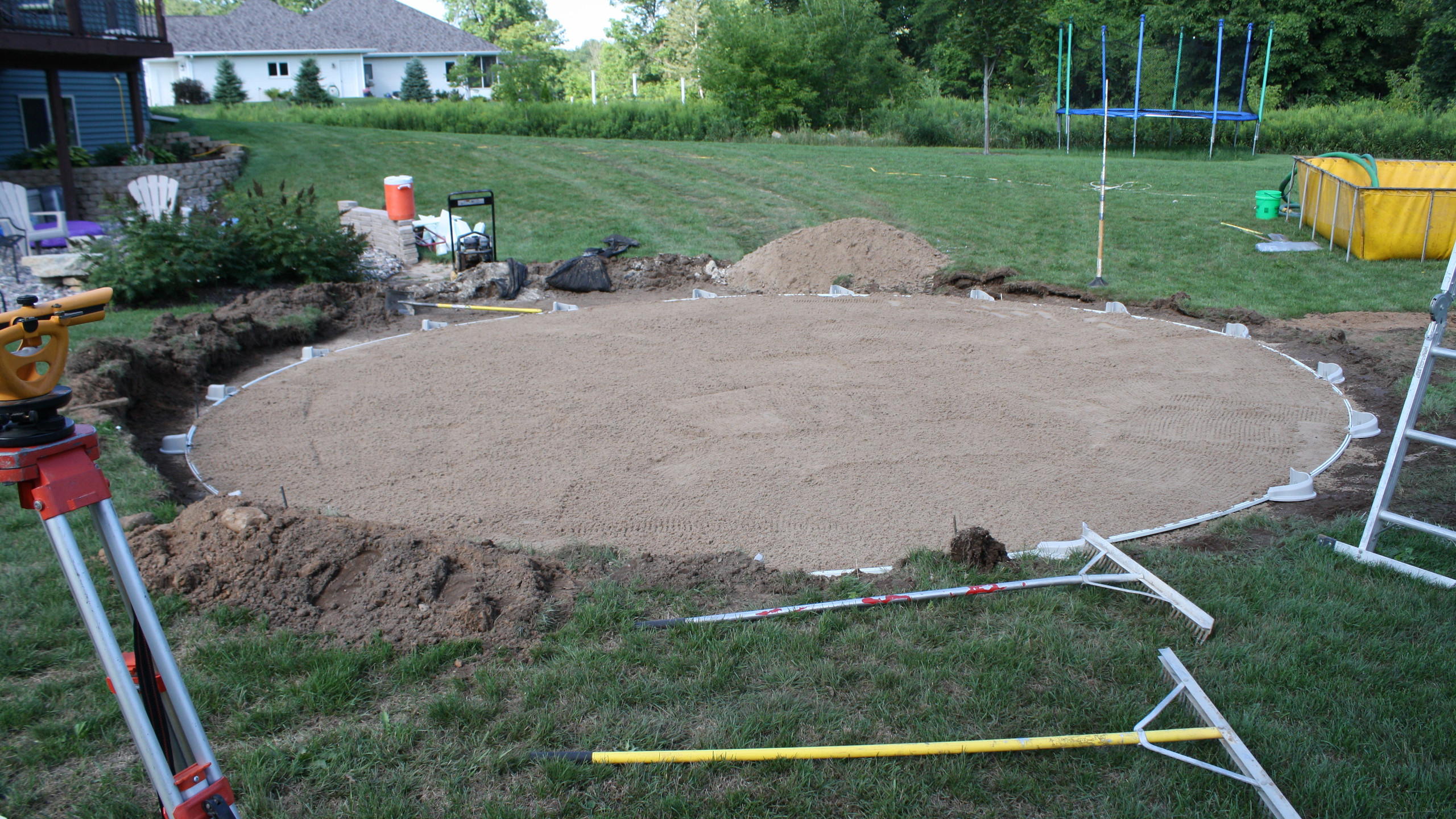 Now that we unloaded the sand we now place the sand inside the bottom track and rake to a uniform thickness.