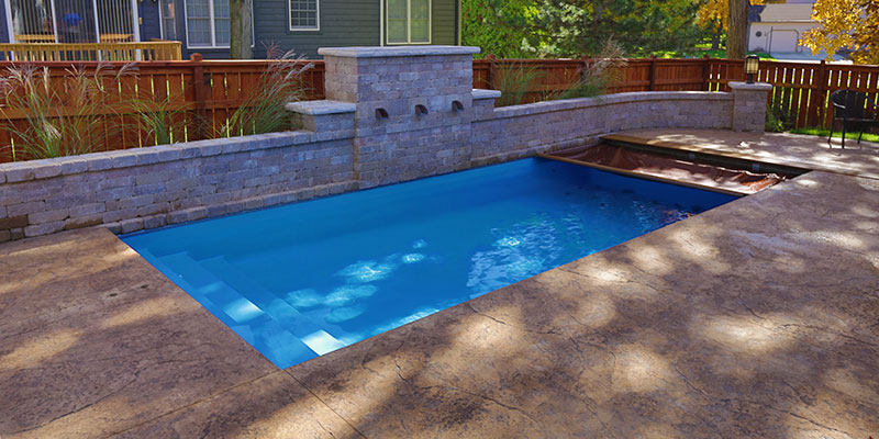 The San Juan Wylela Fiberglass Pool in Lagoon Blue with raised wall and water features and a Coverpools Automatic Pool Cover.