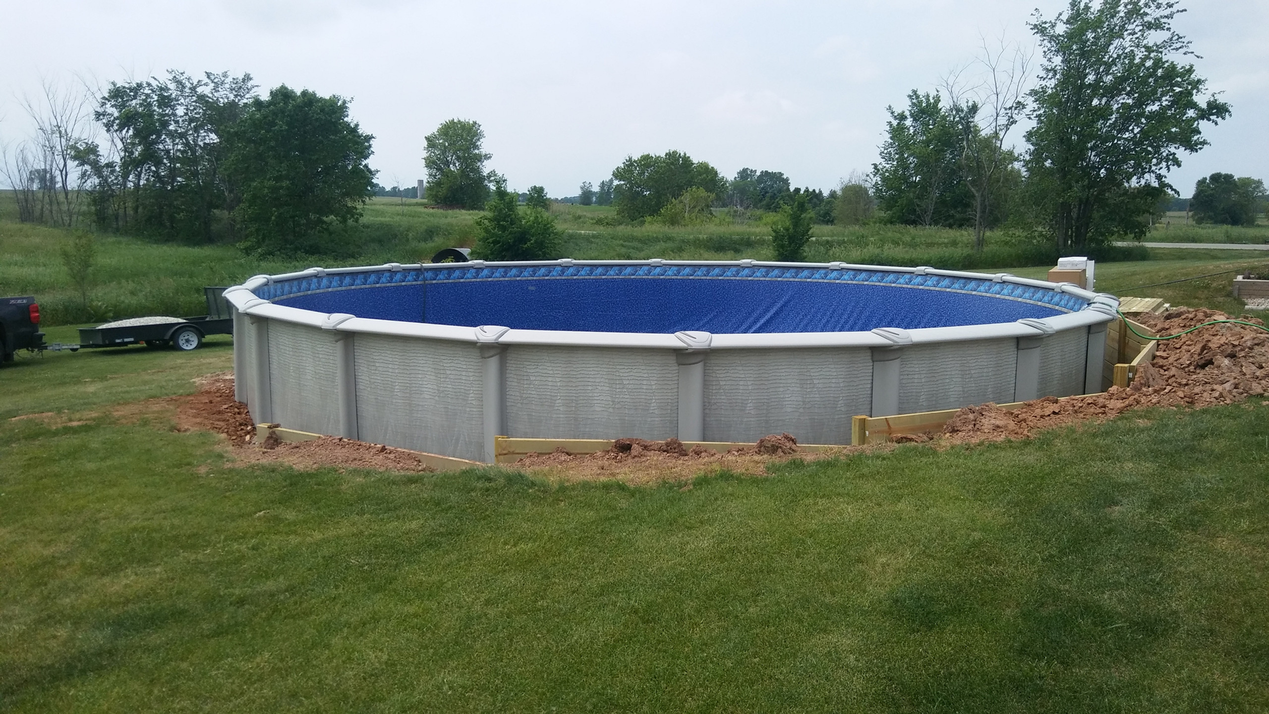 Another 30' Evolution Above Ground Pool by Pool Pros. Pool Pros built this pool in the town of Eaton WI in 2017. This pool was unique as it required us to excavate over 3' into the side of a hill and build a retaining wall to hold back the exposed dirt.