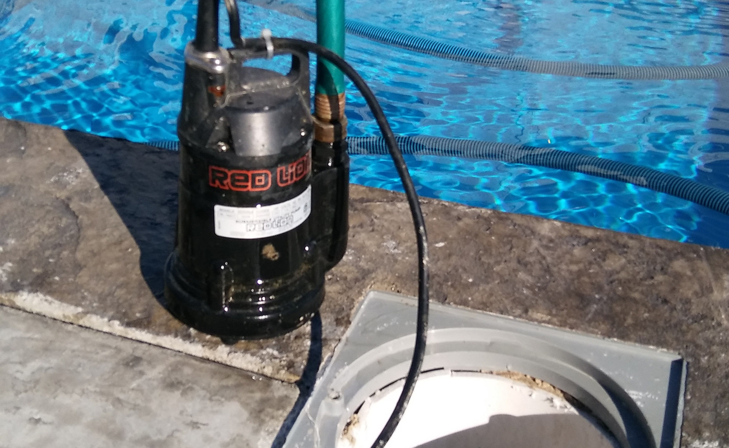 """This 8"""" diameter schedule 40 pvc pipe runs to a depth that is 24"""" deeper than the pool. It is finished of at the pool deck with a skimmer lid. This allows the ability to remove ground water with a submersible pool pump  at any time. It also acts as a hydrostatic reliefe valve that is 4 times the size of one used in a typical concrete pool."""