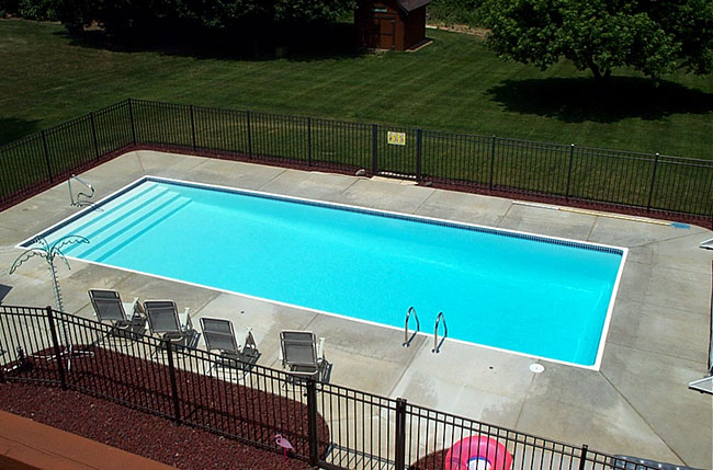 The San Juan Oceanside Fiberglass Pool in white with broom finished concrete decking