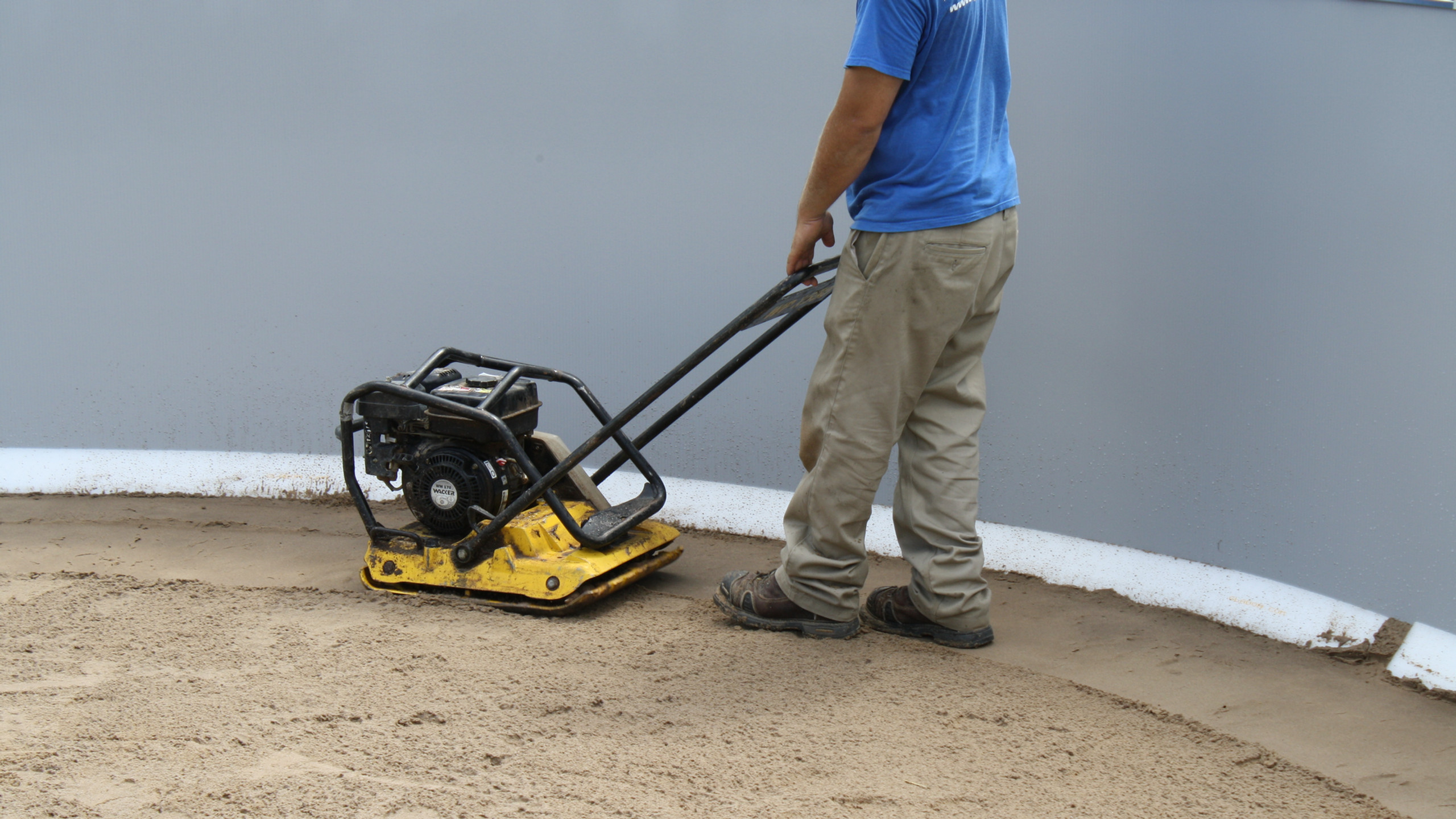 Now we use a plate compactor to compact the sand and get a good firm base.