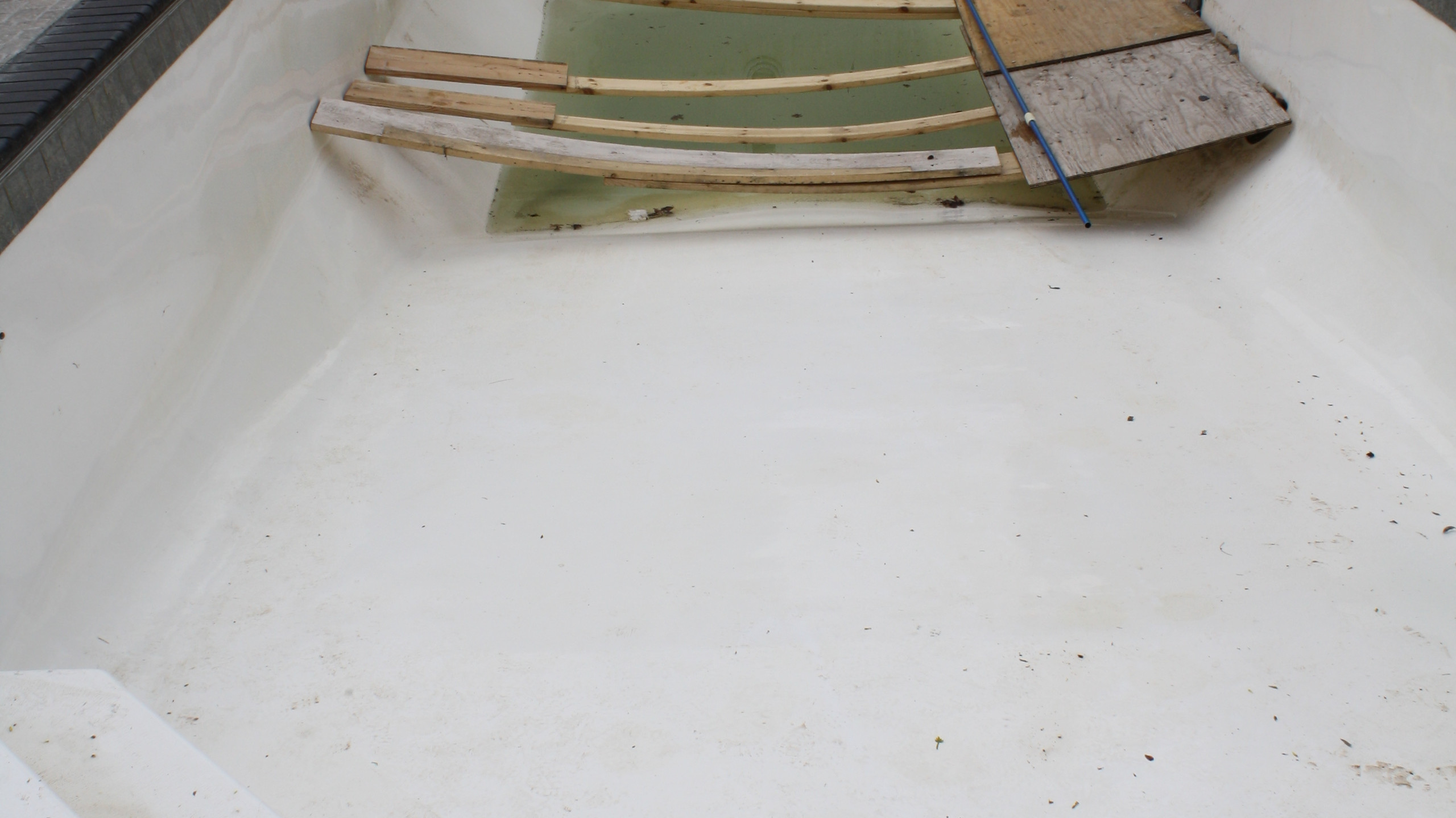 This fiberglass pool built by Siesta Creations in Algoma WI was severely damaged for 2 reasons. There was a high water table with no way to pump out ground water and an inexperienced Service Tech from Premiere Pool Service in Denmark WI drained the pool. The pool was backfilled with sand so when the water was removed formthe pool the sand on the sides of hte pool liquifide and began heaving on the pool. The liguifide sand cause a large 8' long buckle and crack down the floor of the pool.