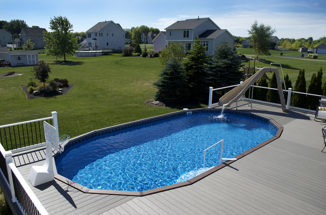 A Fox Ultimate Oval Above Ground Pool with surrounding composite deck.