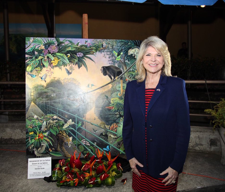 US Ambassador to Costa Rica, Sharon Day, poses with a rainforest painting by Deirdre Hyde