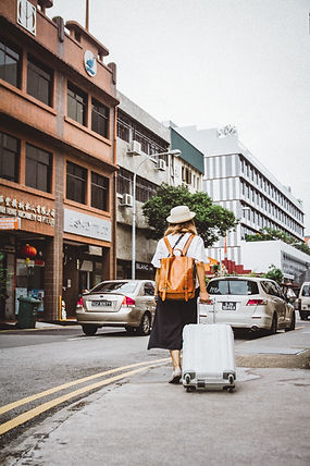 Woman dragging suitcase in an Asian street scene.