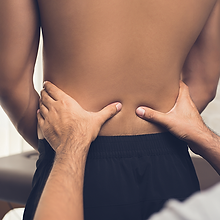 Physiotherapist checking a young male's lower back and spine