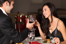 A couple toasting wine over dinner