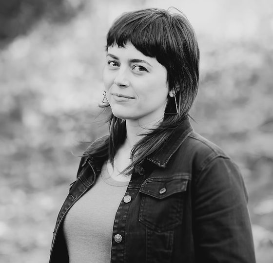 A black and white photo of Dani Allen from the shoudlers up. She has brown hair and a jean jacket.
