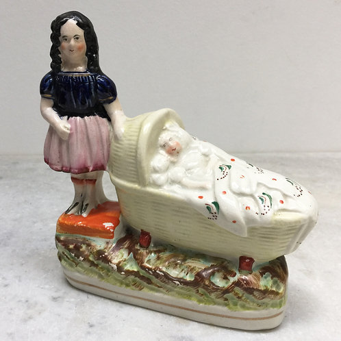 Staffordshire Figure Of A Girl & A Baby In A Crib