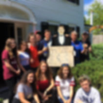 Group of young people posingoutside of house with a cadboard cut out of a man in a suitholding a cardboard FFI sign.