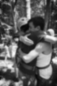 Black and white image of two young men hugging. They are both wearing rock climbing harness and one wears a helmet.