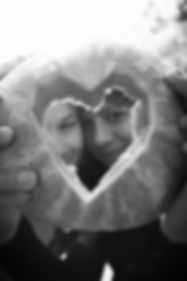 Two young women holding a watermellon shaped nto a heart with the girls looking through it smiling in black and white.