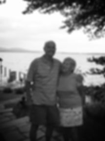 An oler couple stading outside on deck posing and smiling for picture in black and white.