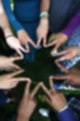 Picture of many different skin colors holdig their handsin a peace sign, forming a star like image with fingers.