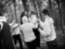 Group of young people juming and laughing in the woods while doing an activity in black and white.
