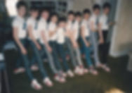 Image shows several young teens standing in a line in matching outfits.