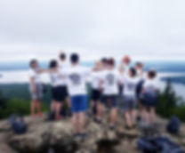 Group of young people on the top of a mountian after hiking, looking at the amzing view.