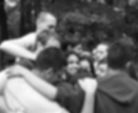 Black and white image of a group hug. One young woman in the middle is looking at the camera.