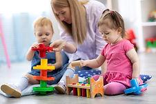 Nursery children playing with teacher in