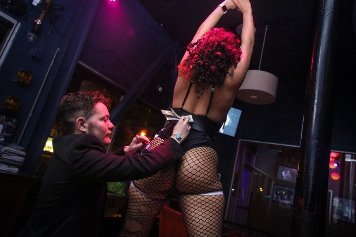 """Storment tips Jazmine Vieira, a queer nightlife dancer, during Vamp Mondays at Beaux in San Francisco, Calif. on May 13.  """"I do [Vamp Mondays] in the labor of love"""" says Storment. (Photo: Adelyna Tirado)"""