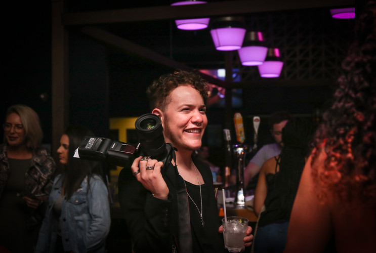 Storment smiles while photographing Vamp Mondays at Beaux in the Castro, San Francisco, Calif. on May 13.  Aside from hosting Vamp Mondays, Storment also photographs and films for the weekly party, and is generally known for photographing queer nightlife events and parties. (Photo: Adelyna Tirado)