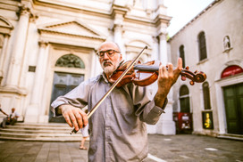 A senior street violinist plays his instrument for money in Venice, Italy on June 16. With Italy being such a high tourist attraction country to visit, street artists highly rely on the visitors to help make ends meet. Ages of street artists range from children to seniors. (Photo: Adelyna Tirado)