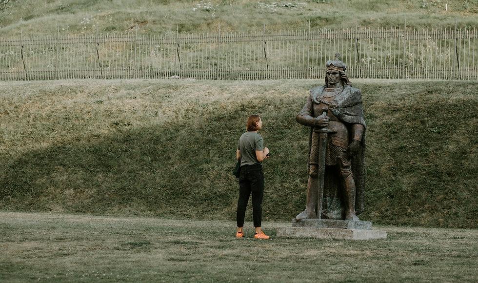 Vyras ir Vytautas Didysis žvelgia į vienas kitą. Vyras ekskursijoje