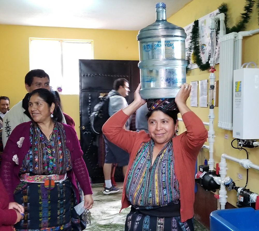 A mother carries clean water from the LWW system
