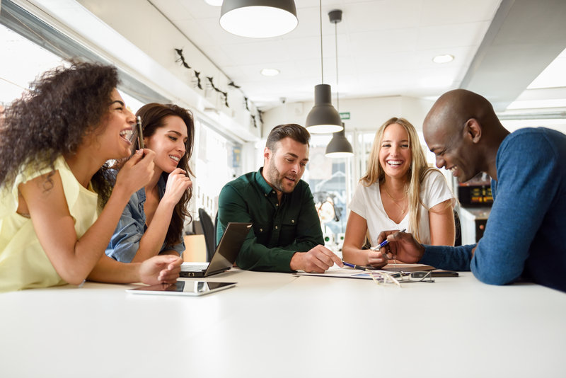 a group of five people sitting around the table tossing ideas