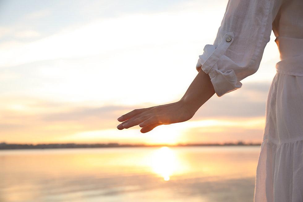 Young woman near river at sunset, closeu