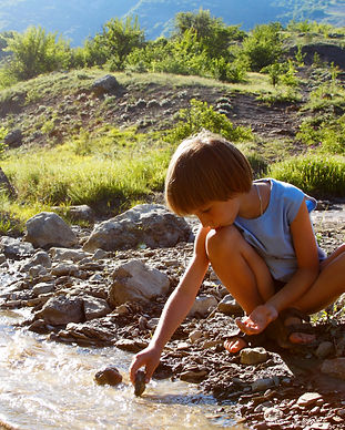 little boy play with flowing water in mo