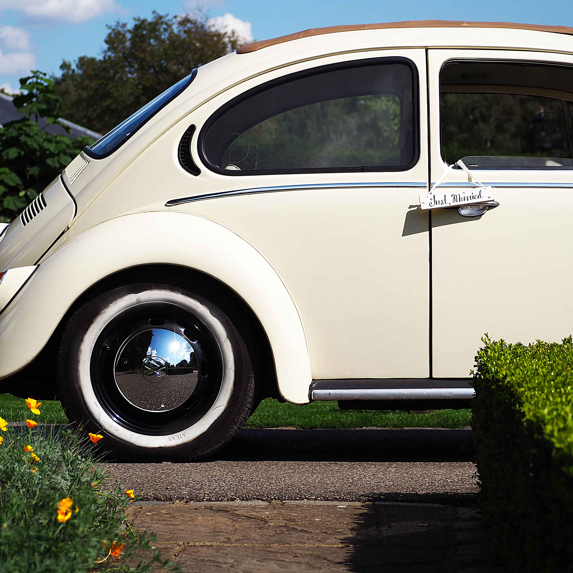 Arriving in style in a Volkswagen Beetle wedding car.