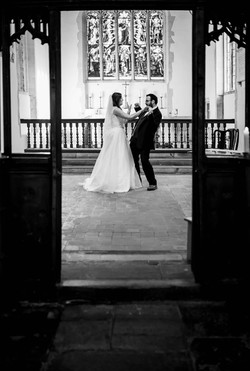 Black and white of the bride and groom celebrating
