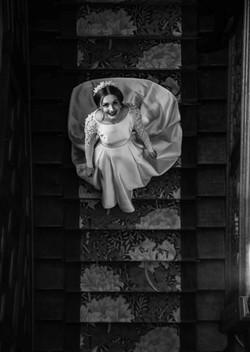 Gorgeous bride walking down the amazing staircase at Eynsham Hall