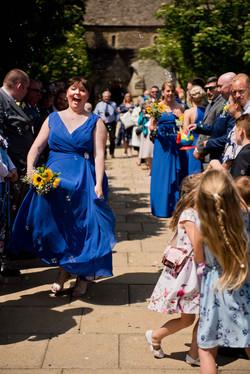 Maid of honour dancing through confetti