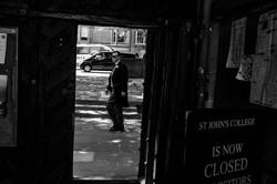 Street photography framing of the groomsman walking through Oxford
