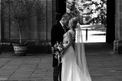 Bride and groom share a kiss at Trinity College