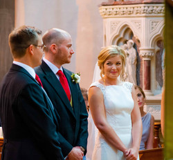 A bride giving a cheeky smile to her husband to be at The Oratory in Oxford