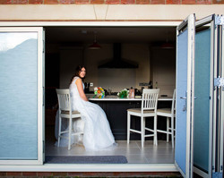 Bride in her dress in the kitchen waiting to go to the church