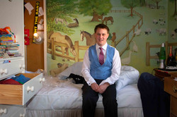 A fun portraits of the groom waiting in his childhood bedroom.