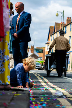 Child plays with confetti in the street outside The Oratory in Oxford