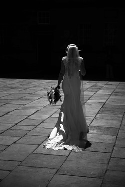 The gorgeous bride walking through the courtyard at Trinity College