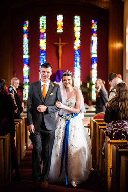 A very happy bride and bridegroom walking together down the aisle