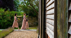 Bridesmaids and flower girl make their way the the wedding breakfast