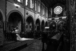 A beautiful wide shot of the couple knelling at the alter of The Oxford Oratory