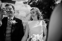 The brides veil flapping in the wind as they drive through Oxford