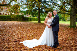 Bride and groom have a cuddle in the Autumn leaves at Easthamstead