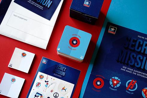 overzicht van al het drukwerk dat we maakten voor kinepolis. De achtergrond is rood en er liggen blauwe kaarten, post its, stickers en een poster op. Op het blauwe kaartje staat operational excellence. Dit is een project op maat van de grafisch ontwerpers van stardust.